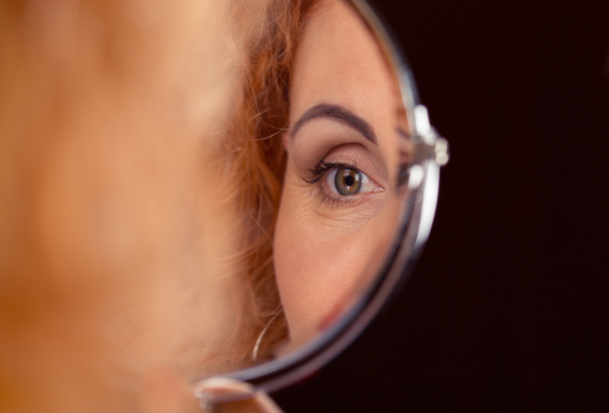 Image of woman's eye in a mirror to reflect Eyelid Surgery, or Blepharoplasty