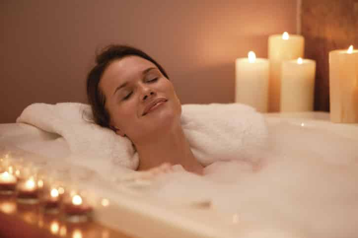 Woman in bubble bath with candles
