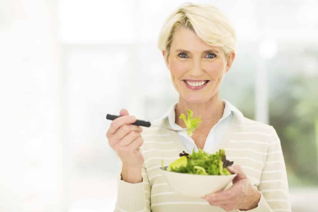 senior female vegetarian eating salad
