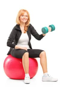 Smiling woman exercising with a dumbbell and sitting on ball