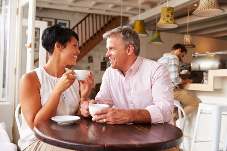 Middle aged couple in a cafe enjoying a coffee