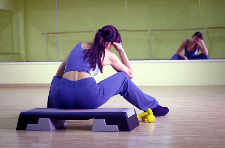 Woman-sitting-on-step-in-gym-resting-head-on-hand,-rear-view