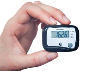 Close-up Of Hand  Holding Digital Pedometer On White Background
