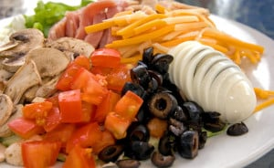 Beautiful chef salad with tomatoes, sliced egg, cheese, olives, mushroom, turky & ham.