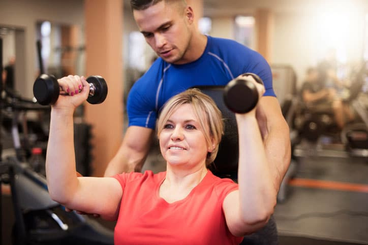 Woman lifting weights with a personal trainer
