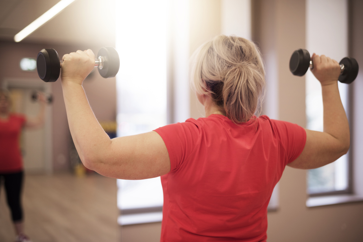 Rear view of Woman lifting weights as part of a weight lifting routine