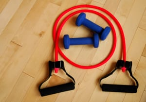 Red Resistance Band and Blue Weights on Gym Floor
