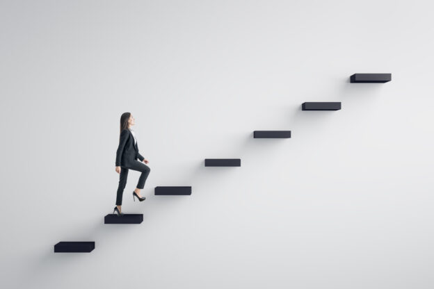 Woman climbing stairs or a corporate ladder - types of leadership