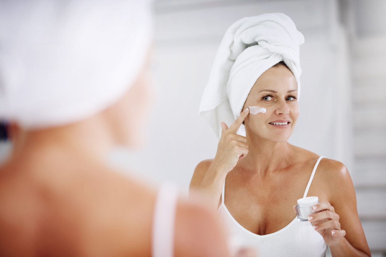 Best drugstore skincare products, woman applying face cream with towel on head