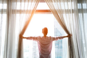 Woman opening curtains to start her morning routine