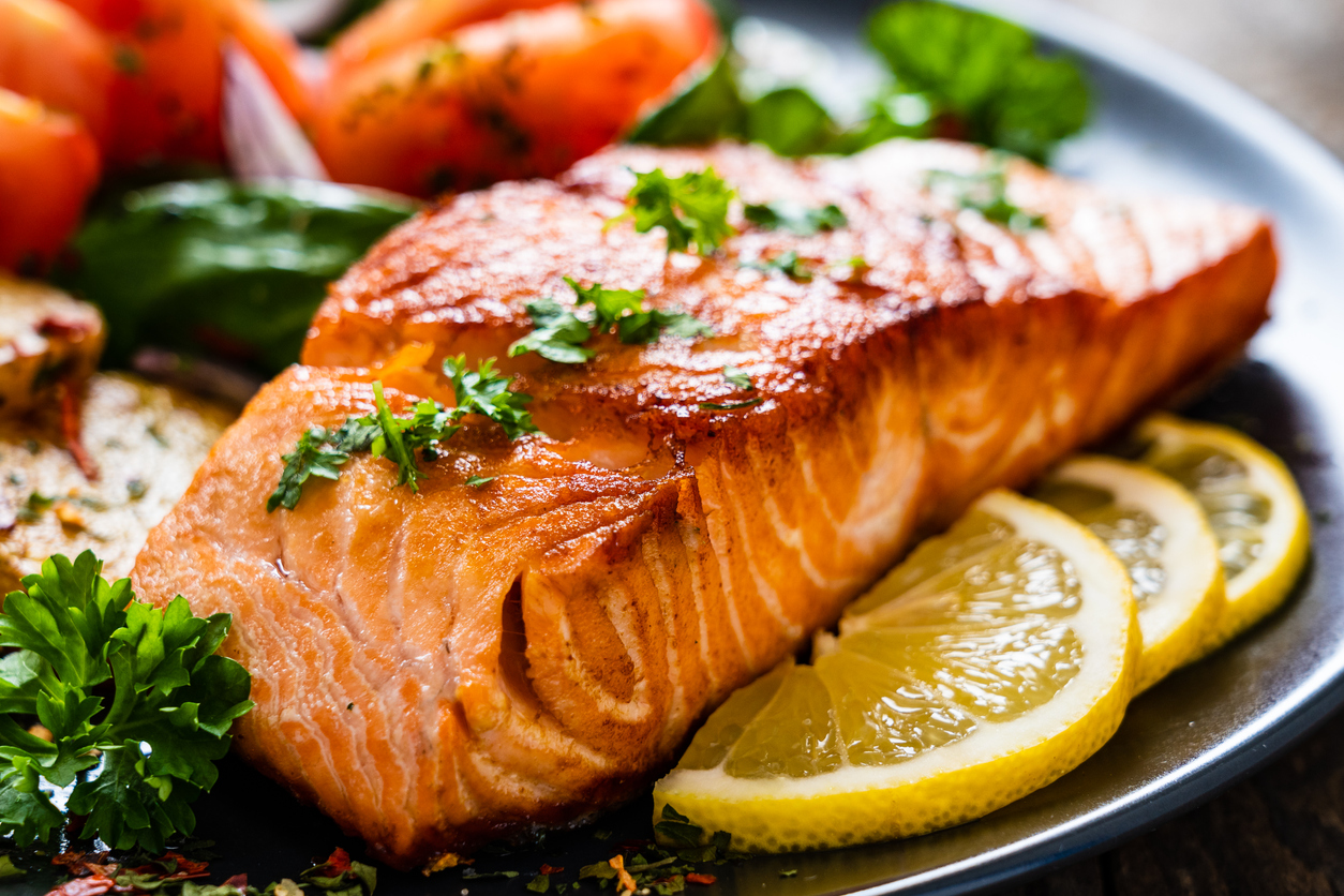 Grilled salmon on a bed of vegetables can help lower your cholesterol