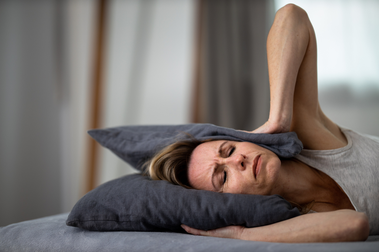 Woman with pillow over head, tinnitus, ringing in ears, headache, pain