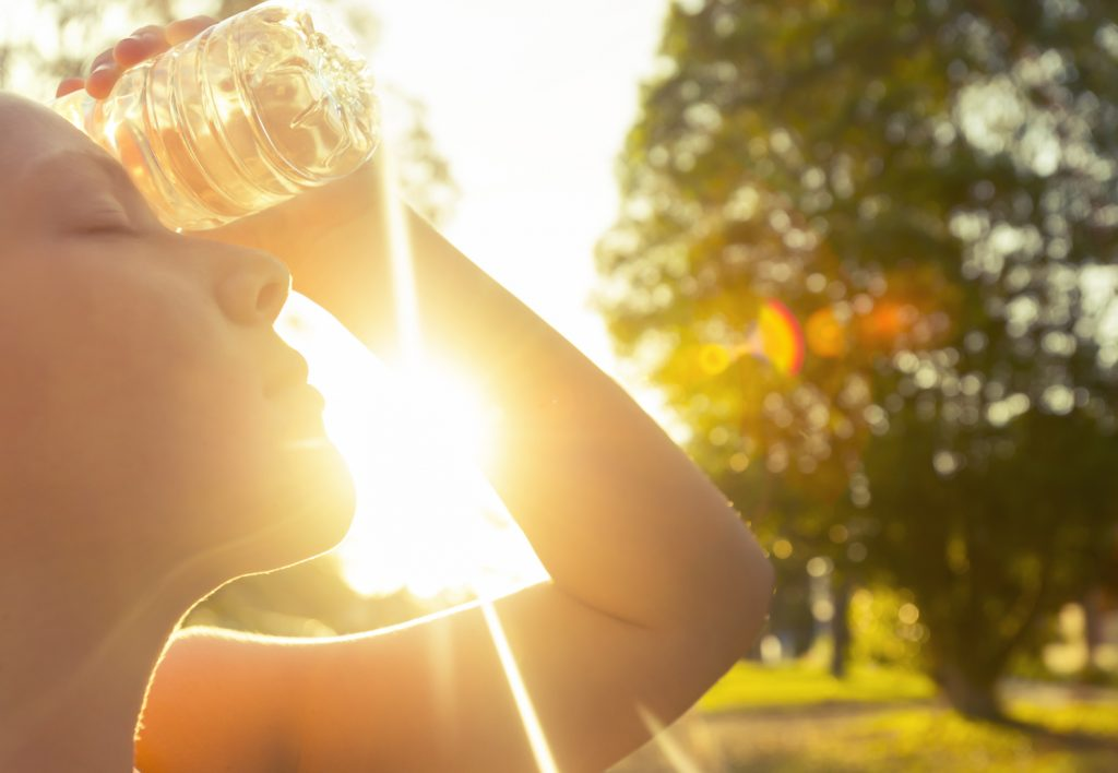 woman using water bottle to cool down during a hot flash