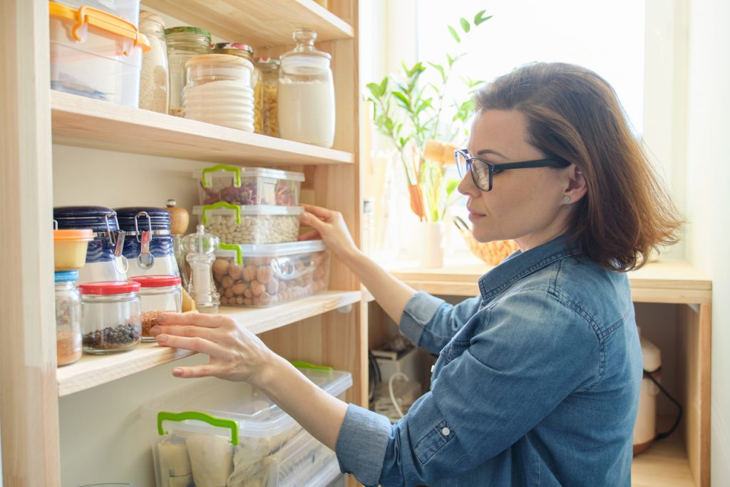 Woman looking at cupboard to check out her selection of foods.