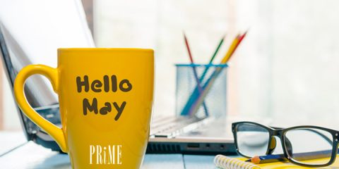 yellow coffee mug with month of May written on it