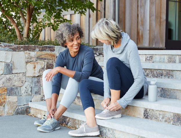 women sitting on steps making friends after 50
