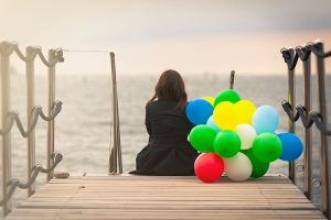 women sitting on a dock with balloons