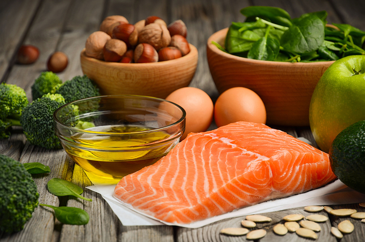 Healthy foods - Salmon with vegetables, olive oil, and nuts