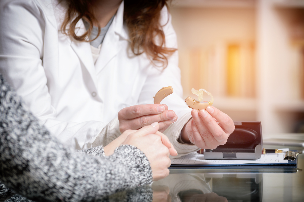 Woman holding a set of hearing aids as they discuss hearing loss with an audiologist