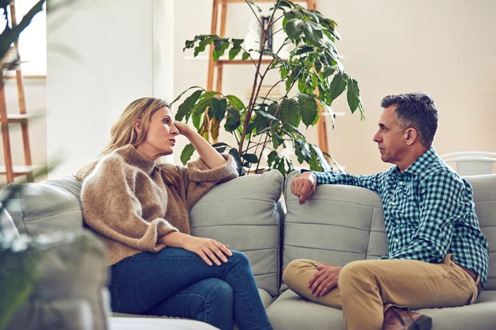 Couple having discussion/argument on the couch because hearing loss can negatively affect relationships