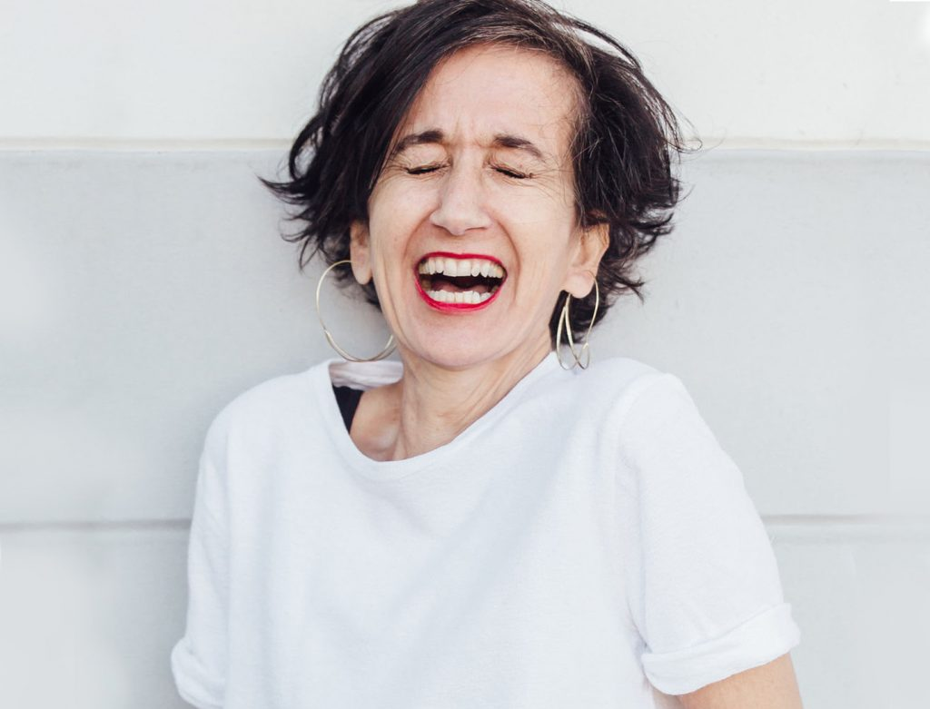 older lady in a white tee with a big laugh