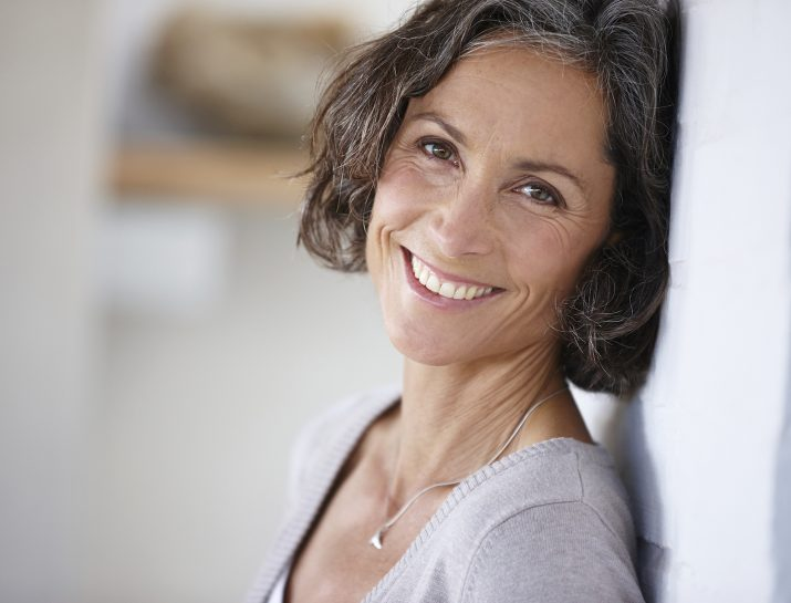 beautiful gray haired woman leaning on a wall