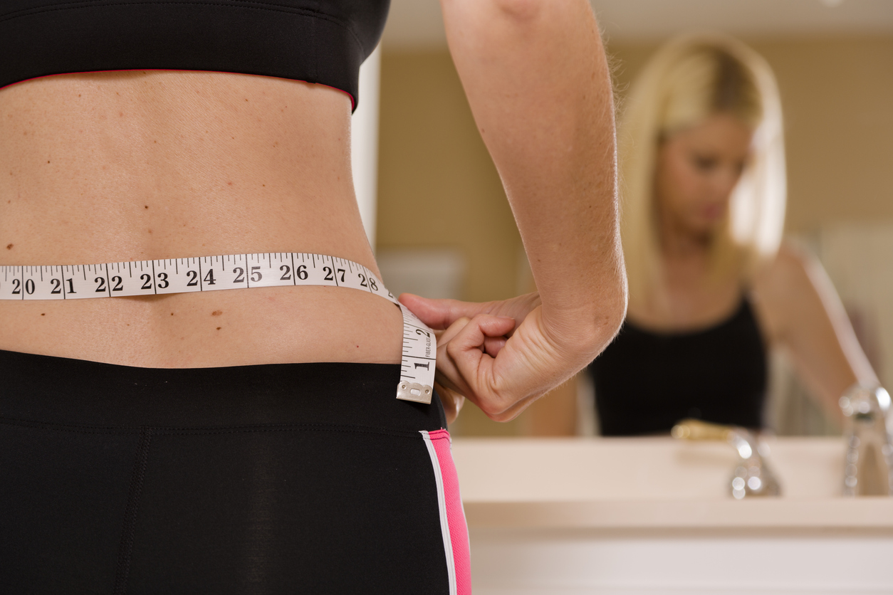 Woman Measuring Waist to reduce belly fat