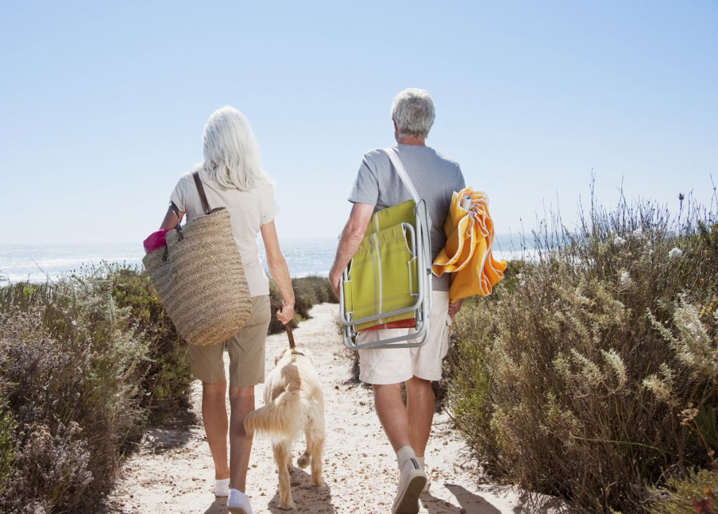 Mature Couple Holding Beach Bags