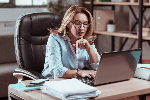 Hard-working businesswoman wearing glasses reading important e-mail