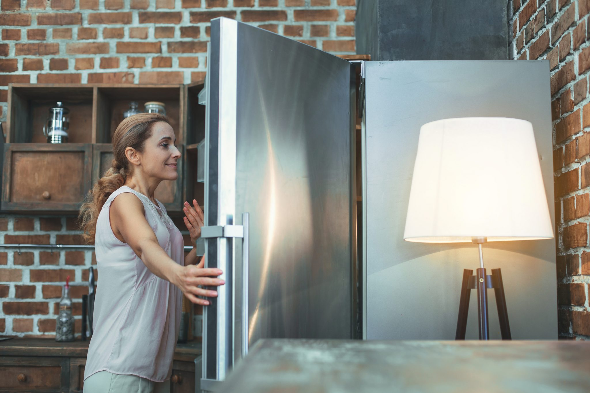Glad mature woman cools off in front of fridge menopause hot flashes