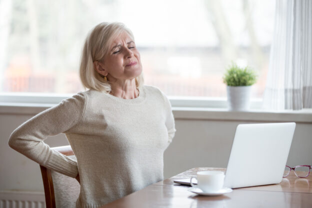 woman holding her back because her posture might be causing it to hurt.