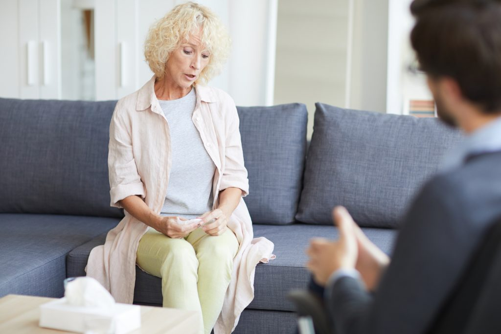 mature woman with curly hair holding napkin and nervously sharing her problems without looking psychiatrist in eye at psychotherapy session for emotional health