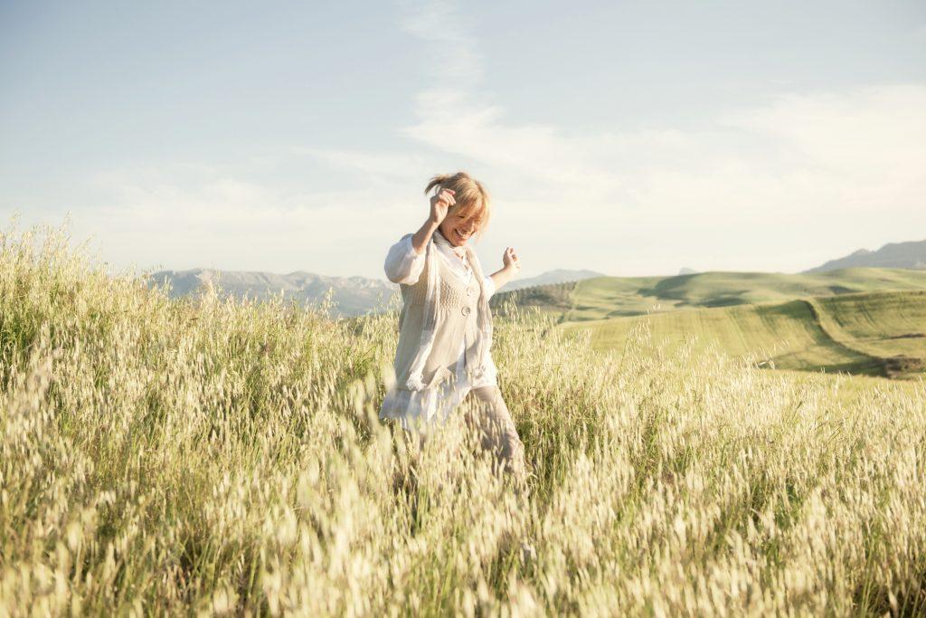 women inspiring women Woman running in grassy field
