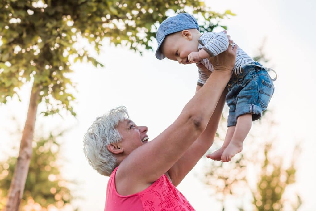 GRANDPARENTING TIPS grandmother is playing with baby in park