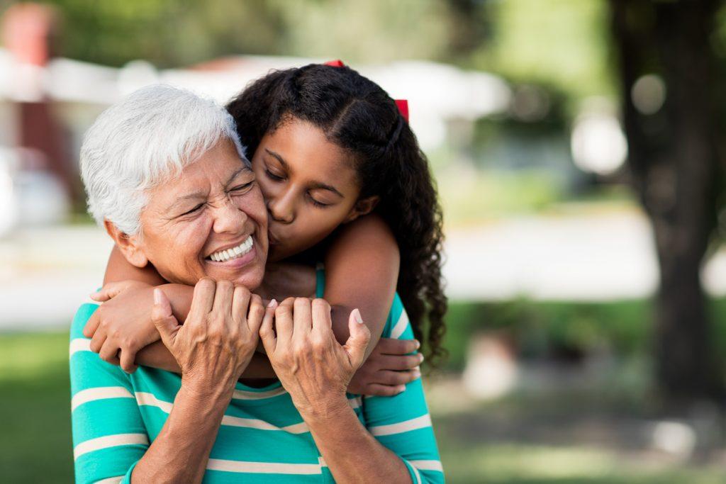 GRANDPARENTING TIPS Loving teen girl embracing and kissing grandmother