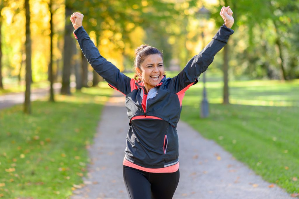 Happy fit woman cheering and celebrating