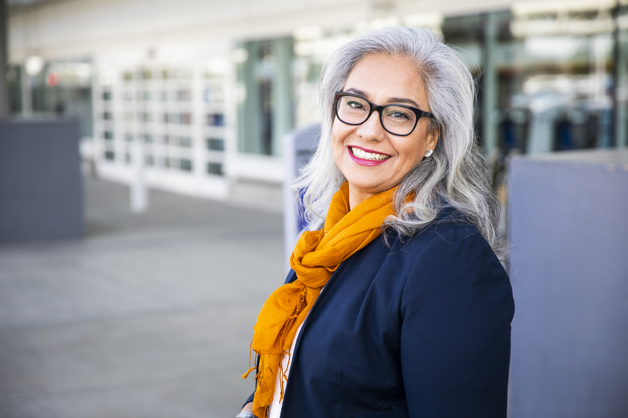 Gray haired woman in a blazer with a fashionable scarf