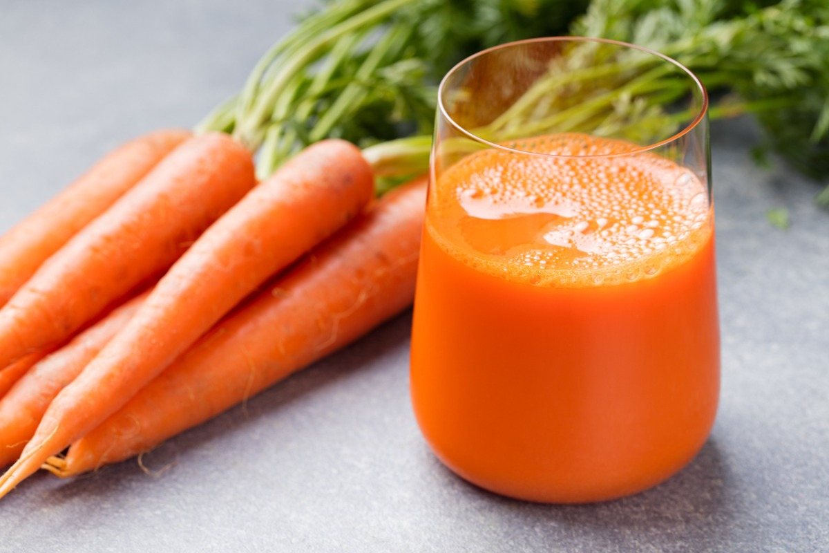 Carrot juice in a glass and fresh carrots beside it