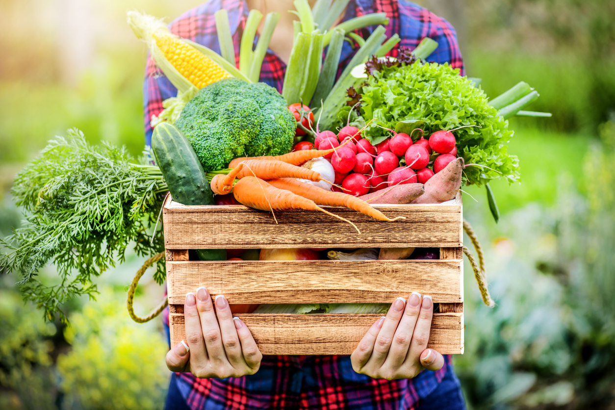 Woman holding a box of vegetables to help lower your cholesterol