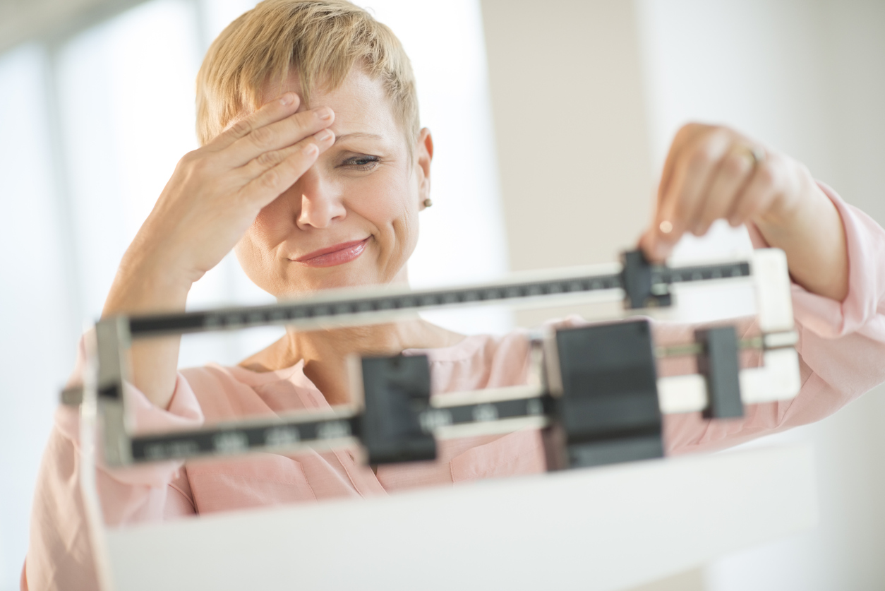 Postmenopausal woman on scale, frustrated because she's unable to lose weight