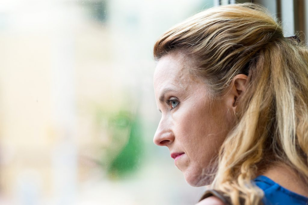 Depressed woman looking out window to show Keratin can be used as a treatment for depression