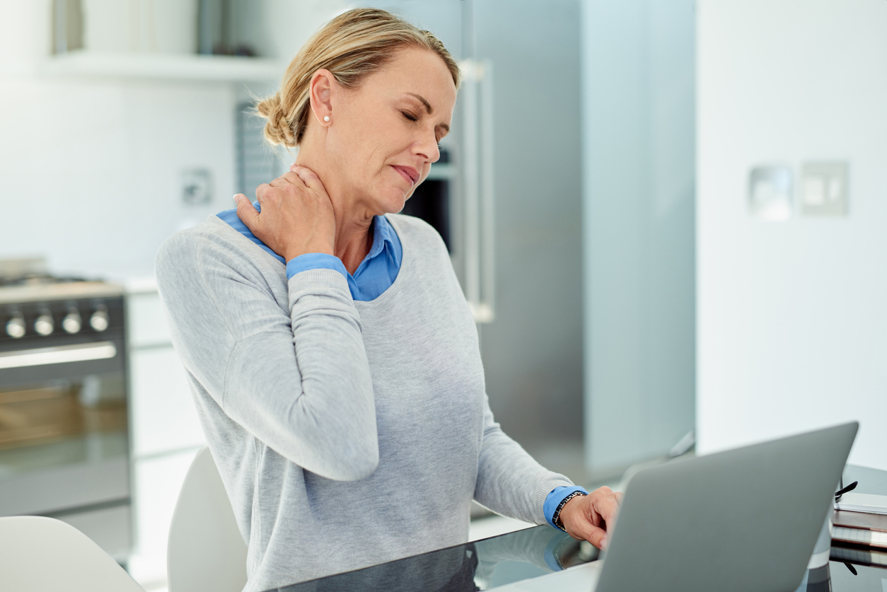 Woman with a sore neck or neck pain from text neck