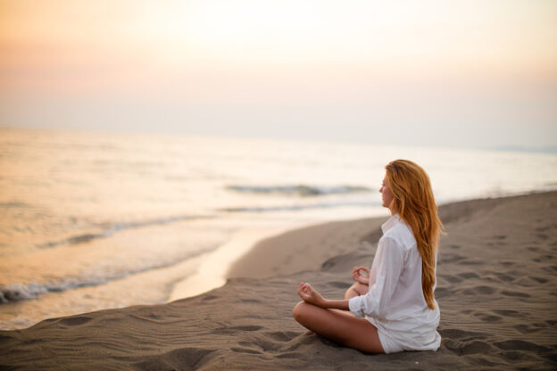 Woman doing yoga on the beach for exercise and hair growth