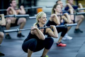 Muscle building workout - woman doing squats with a barbell