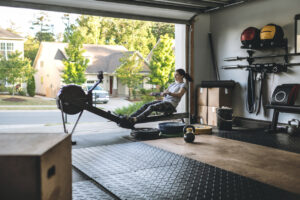 Best exercise equipment - woman in garage home gym working out on rowing machine
