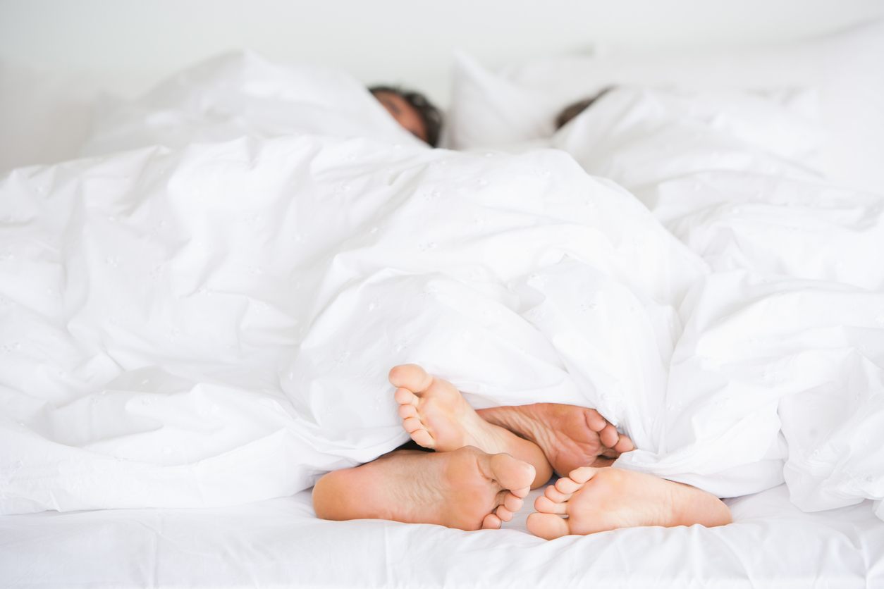 Couple in bed together, showing feet