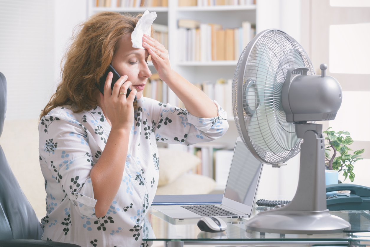 Woman having a hot flash sitting in front of a fan for relief