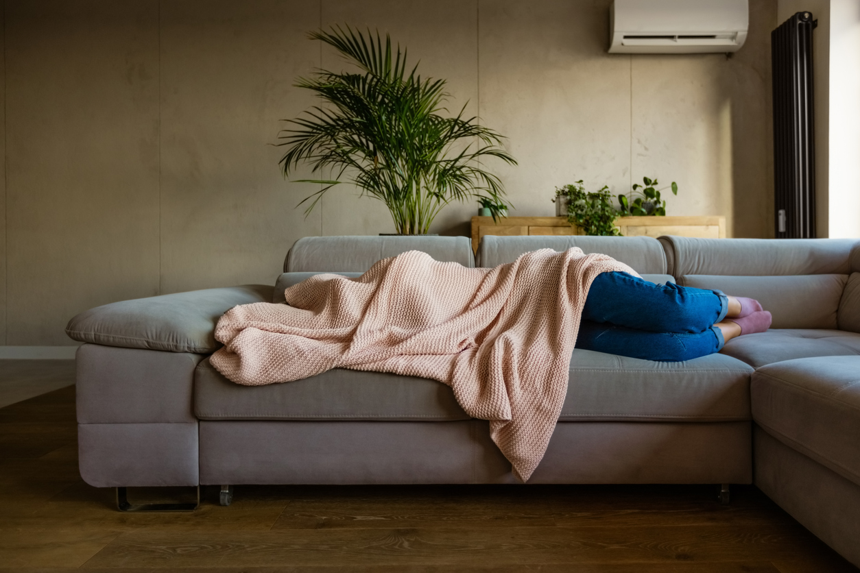 Woman sleeping on couch - crashing fatigue from menopause