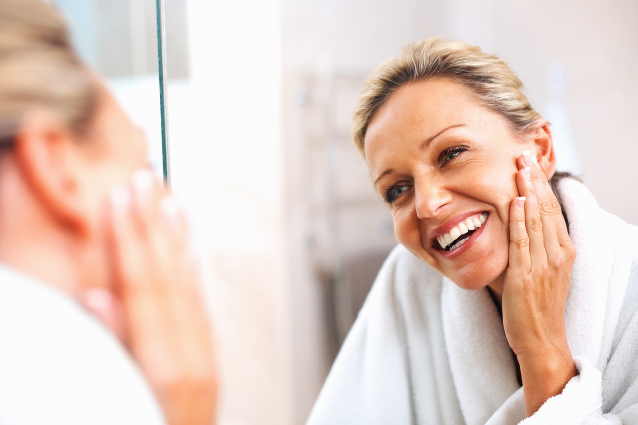 Woman looking at her face in the mirror smiling