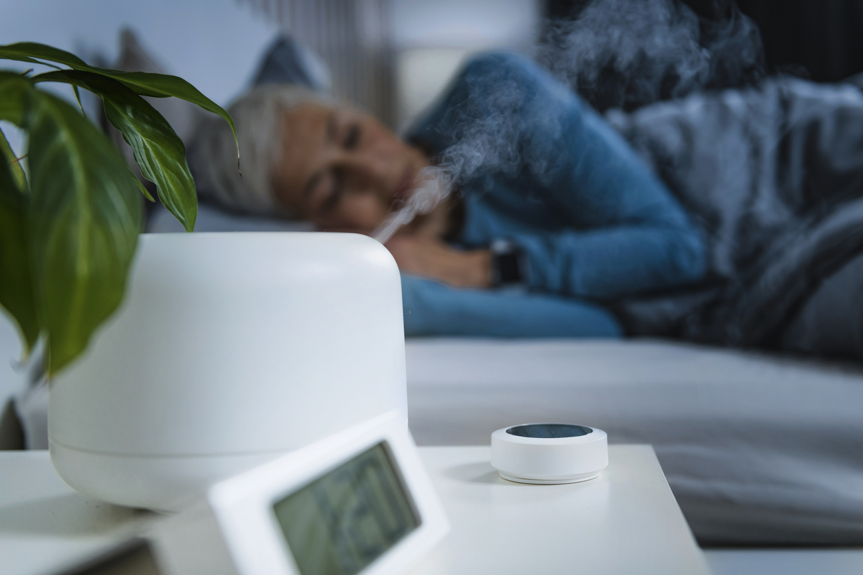 woman sleeping with humidifier to help with menopause and snoring